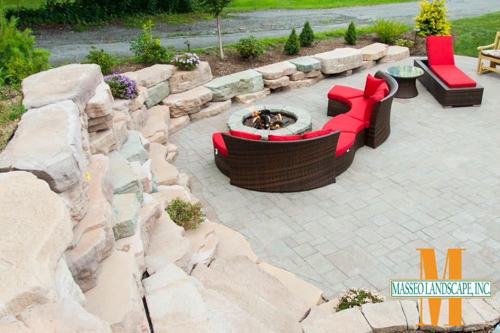 A downward view of a Rosetta Outcropping retaining wall and Cambridge Pavers patio with a circular fire pit.