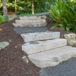 Natural stone textured concrete steps set into a hillside.