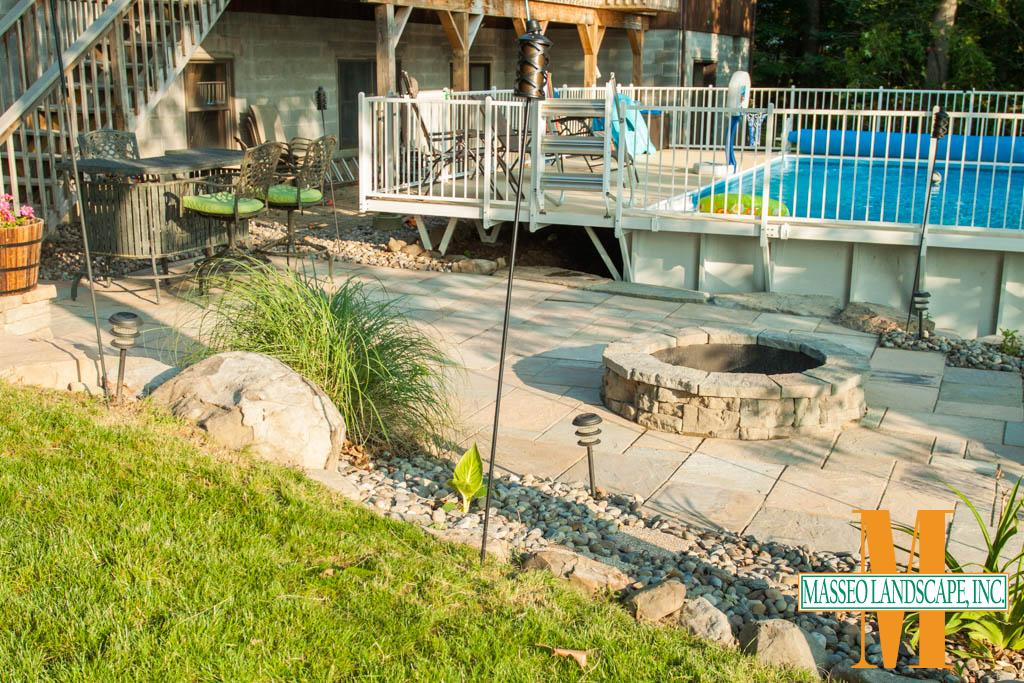 A geometric patio alongside a pool in New Paltz, NY with a circular fire pit, and river rock beds with natural stone curbing.