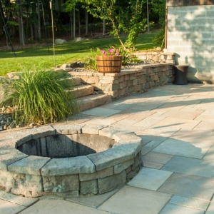 A Rosetta Belvedere fire pit on a rectilinear patio with a Belvedere retaining wall and Rosetta Irregular steps.