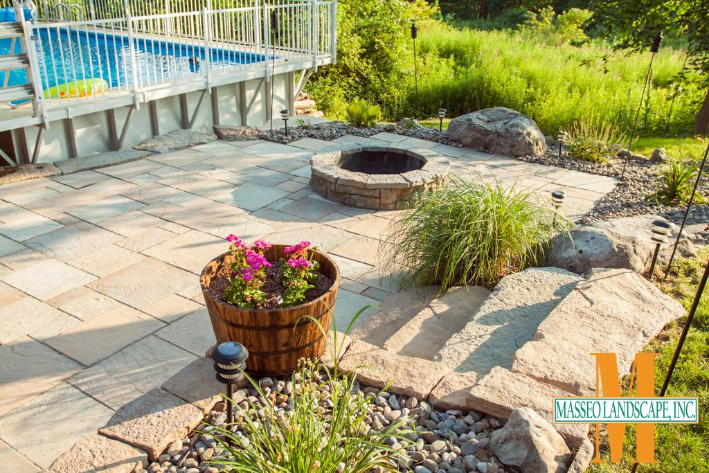 A rectilinear patio built from Rosetta Dimensional Flagstone pavers with a circular fire pit and surrounded by river rock planting beds.