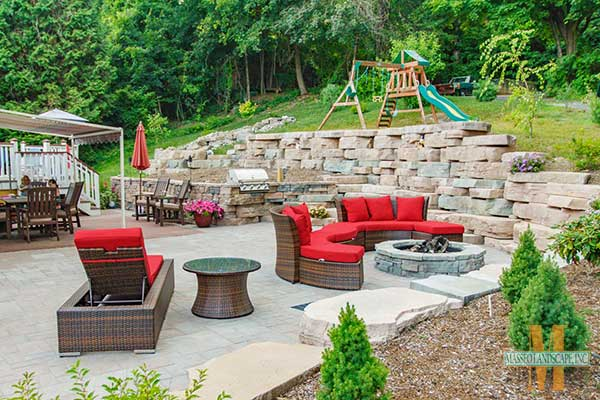 An outdoor living space with retaining wall, fire pit, and patio.