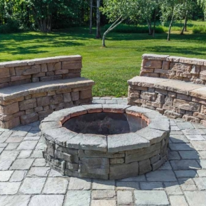 Two stone benches and a circular fire pit.