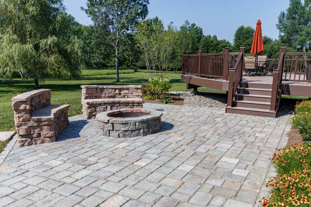 A precast concrete patio with stone benches curved to match a circular fire pit.