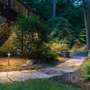 Outdoor lighting scheme in yard with stone walkway and planting by Masseo Landscape, Inc.