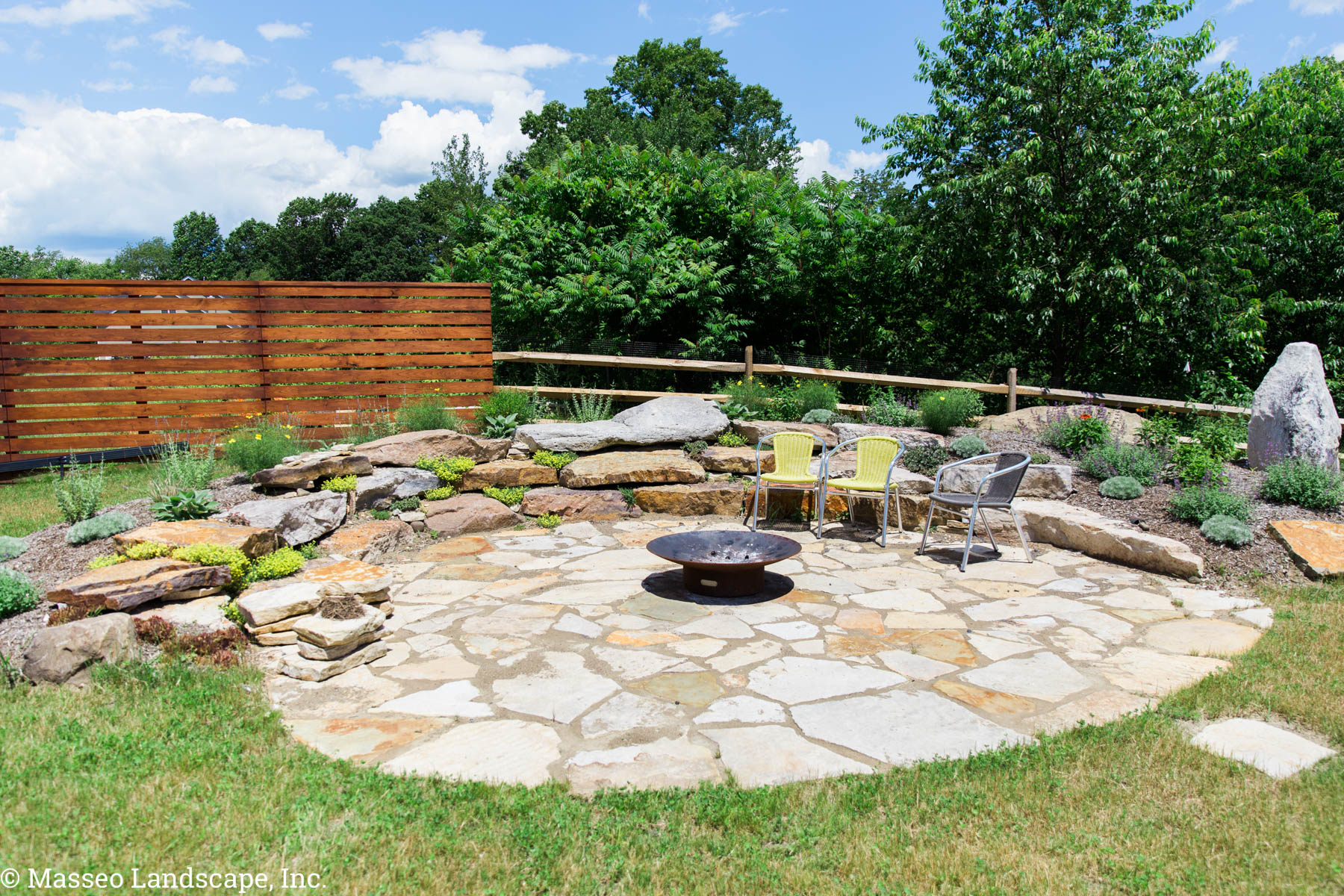 Circular natural stone patio installed by Masseo Landscape, Inc, Gardiner Landscape Contractor