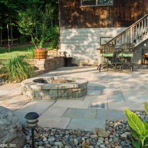 Poolside patio with a fire pit designed and installed by Masseo Landscape, Inc.