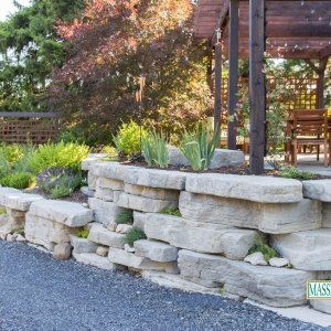 A rustic pre-cast concrete retaining wall in High Falls with annuals and succulent plantings.