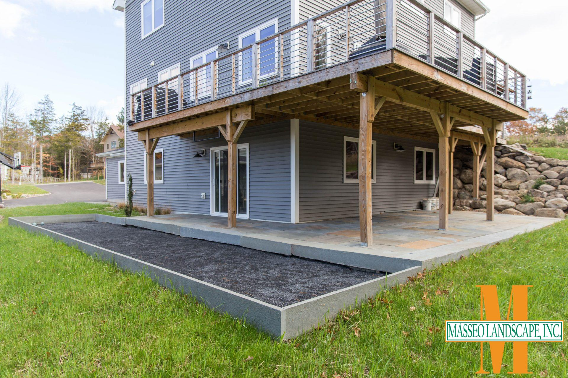 A blue stone patio beneath a second story deck with an attached bocce ball court.