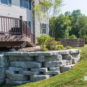 A stone-textured precast concrete retaining wall wrapping around a planting area.