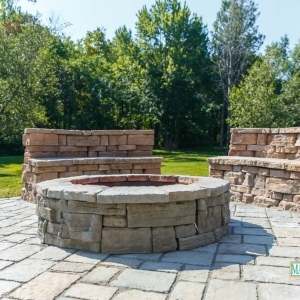 A circular fire pit on a patio with rounded stone benches.