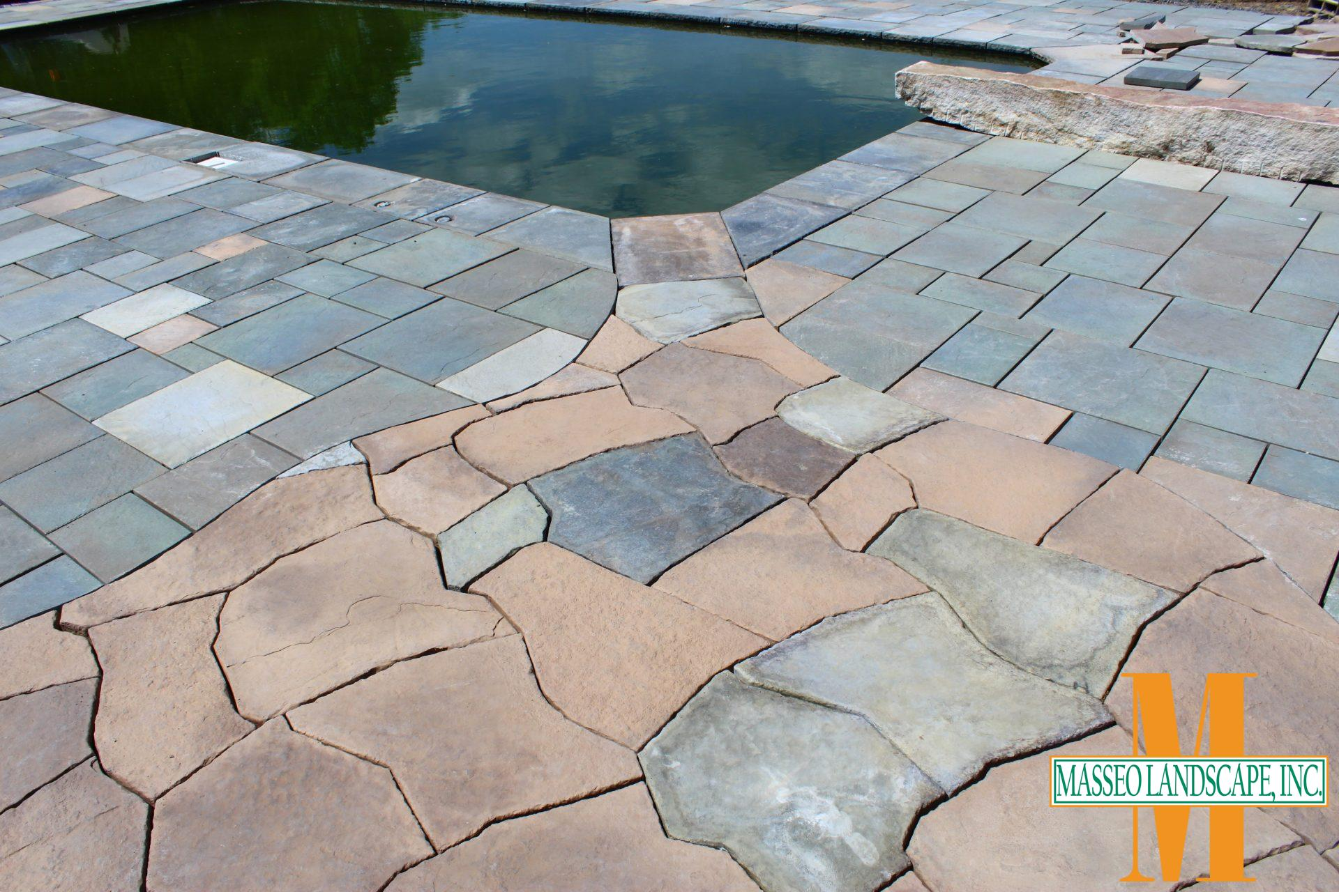 A pool patio featuring a mixture of geometric and naturalistic precast concrete pavers.