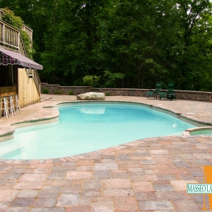 A paver pool patio with a surrounding wall.