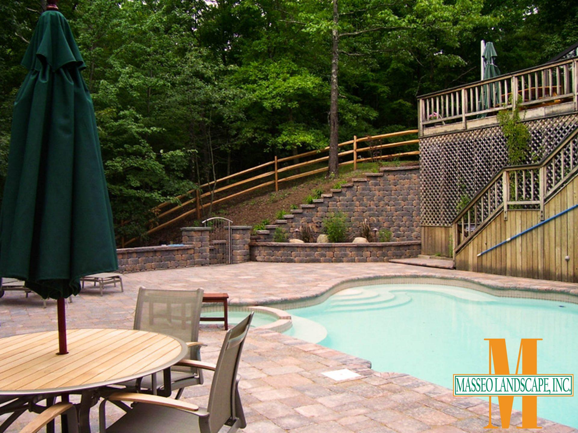 A paver pool patio with a matching hillside retaining walls and walled planting bed.