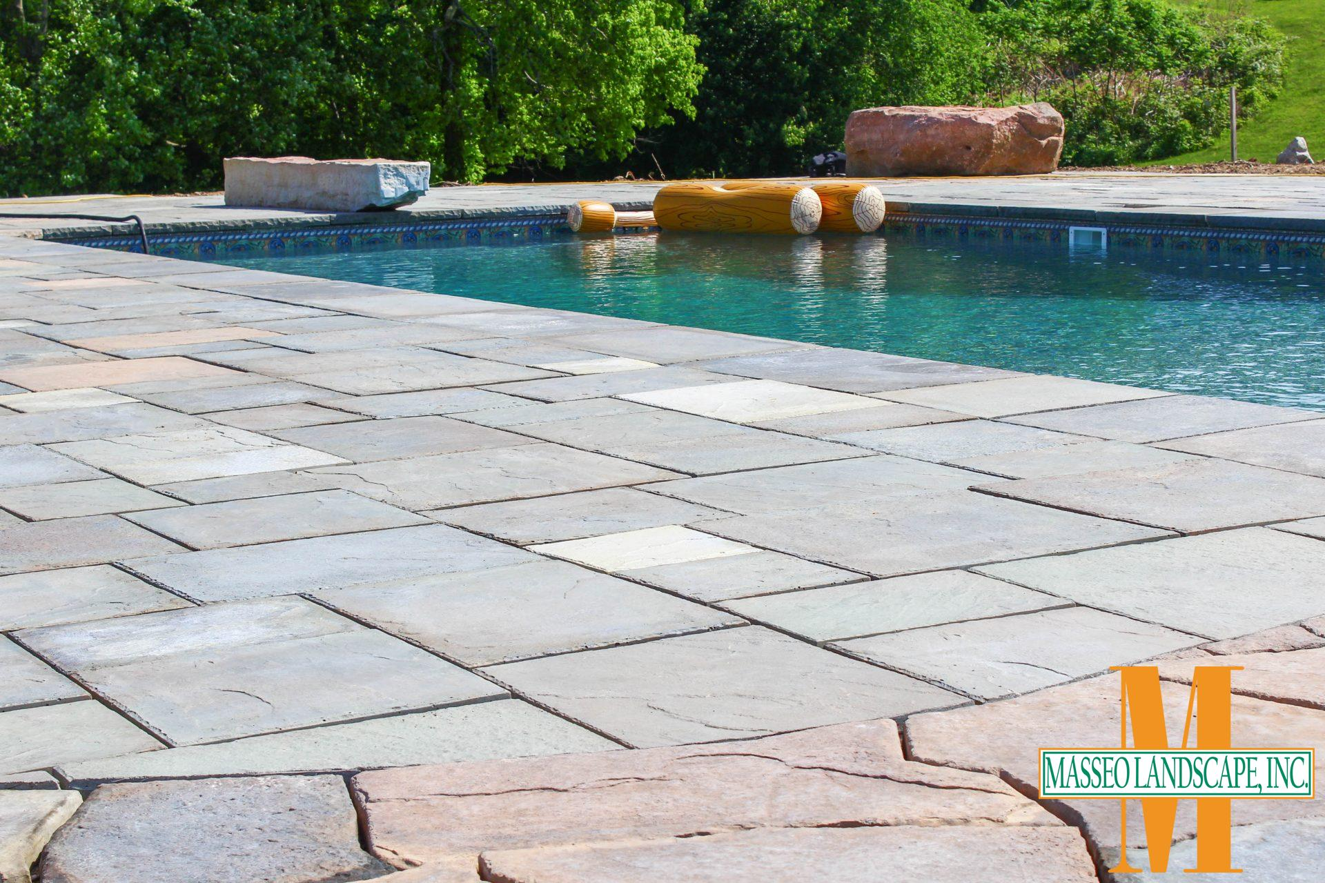 A mixture of geometric and rustic precast pavers in a pool patio.