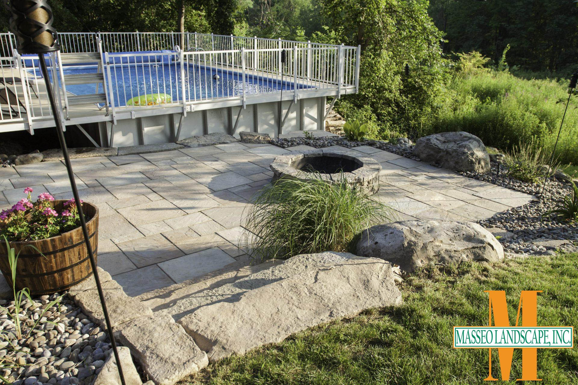 A precast concrete patio with geometric pavers and a circular fire pit beside a pool.