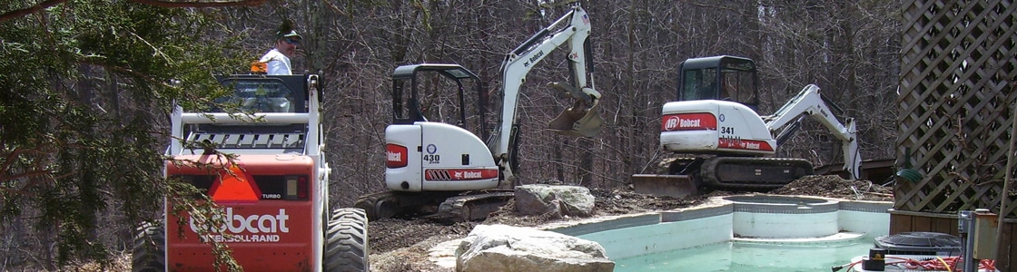Image of Masseo machines in action, regrading the area around a pool.