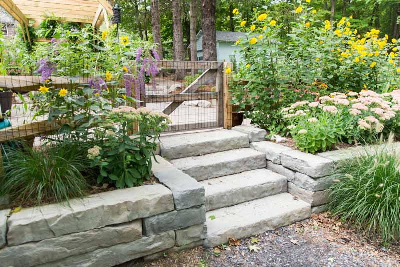 Pre-cast concrete retaining wall and steps to a patio, by Masseo Landscape, New Paltz Landscaping