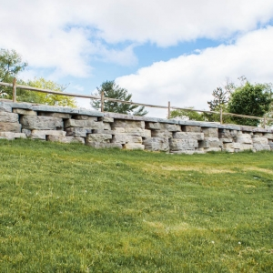 A rustic pre-cast concrete retaining wall with a split rail fence on a grassy slope.