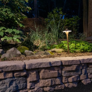 "A stone texture retaining wall with a ""China Hat"" path light."