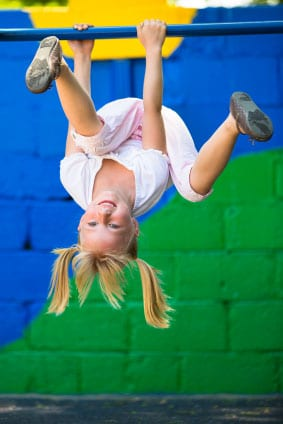 Image of young girl hanging upside down in playground.
