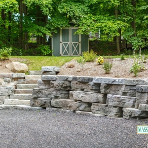 A curved, naturalistic precast concrete stone retaining wall with inset staircase.